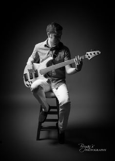 Nick's in-studio black and white photo with bass guitar on a stool. Photo by Bryan's Photography.