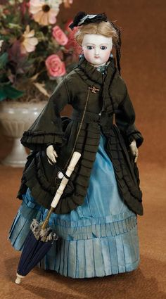 French,circa 1867. Doll wearing original costume and signed C.C. leather boots along with bone-handled parasol,lorgnette,and jewelry.