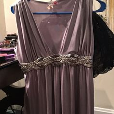Beautiful gray top This top is a beautiful gray stretchy silky looking and feel. It is a sleeveless dressy top, with a plunging neckline, with a braided middle. Has an empire waist, very flattering. Tops Tank Tops