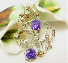 This amazing pendant features a wire wrapped mix of copper and sterling round beads with amethyst colored and clear cubic zirconia gemstones mounted onto a weave of sterling silver wire.      * Pendan