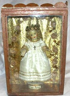 Enfant Jésus .Dans une boîte rustique vitrée. Cire. Il est debout, habillé, tête couronnée de fleurs.Auvergne, Milieu XIXeH : 0,53 x L : x l : 0,36 x Pr : 0,18 m.