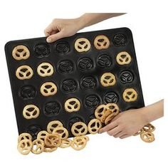 """Whip up mini pretzel-shaped cookies with this baking pan.  Product: Baking panConstruction Material: Carbon steelColor: BlackFeatures: Shapes mini pretzel cookiesDimensions: 0.2"""" H x 16.5"""" W x 13"""" D"""