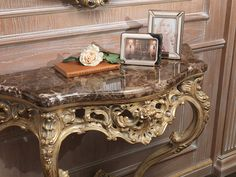 Carved console with Emperador marble top, finishing gold leaf coated in grey