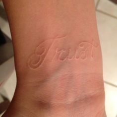 "My ""trust"" tattoo in white on my wrist. Without trust you have nothing in a relationship."