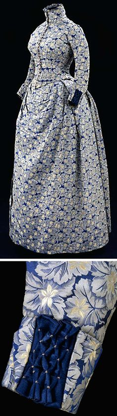 Day dress, Mrs. Francis (?), Britain, ca. 1885. Jacket bodice & skirt of jacquard-woven silk fastened with mother-of-pearl buttons & trimmed with dark blue silk satin decorated with honeycombing. Bodice lined with cotton & whalebone strips. Dense pattern of violets springing from bed of vine leaves. Design woven by powered jacquard loom & is example of good commercially-produced fabric. Victoria & Albert Museum