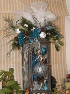 Holiday latern...made with deco mesh, small, medium and large ornaments, floral decor and bells.
