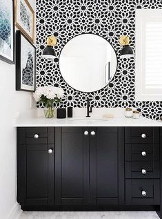 Gorgeous black and white bathroom with brass sconces, black cabinets, white carrara marble counter top, round mirror and graphic floral print tiled wall.