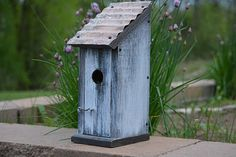 """""""The House of Blues"""" This unique bluebird house is made of rough pine and has a sheet metal roof. There is a latch and eye securing the front which opens to clean out old nesting material. The hole is larger at 1 ½"""" inches. I cut grooves on the inside face which assist the baby bluebirds in climbing out. Approximate dimensions: 15"""" inches tall 5"""" inches wide 6"""" inches deep"""
