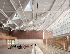 Colourful glass discs are embedded in the clay-tile facade of this school hall near Valencia
