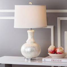 <p>Bring a touch of seaside style to any space in your home with this lovely table lamp. With a design inspired by the octopus, this eye-catching luminary is brimming with nautical appeal. The antiqued turquoise finish gives this lamp a touch of vintaged style, while the wood base and burlap drum shade add a touch of sophistication. </p><p>Whether you want to decorate your beach bungalow or just add a touch of coastal flair to a more traditional ...