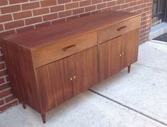 Mid century modern credenza. We believe the wood is walnut. In good vintage condition with age consistent wear. 60L x 19w x 30h  NOTE: SHIPPING IS NOT FREE. For shipping within 125 miles of Lambertville, NJ we can arrange a local truck delivery. Contact us for pricing. If you are outside of that area we can provide estimates on long distance delivery. **local pick ups are free and welcome.  We have locations in Lambertville, NJ, Princeton, NJ and Philadelphia, PA.  Call or contact us prior…