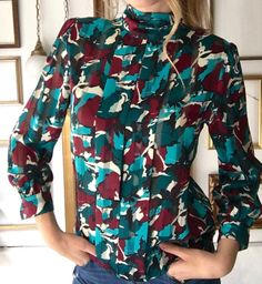 This silkie vintage blouse buttons up the back and features a turtle neck, sheet stripes, and maroon, cream, and teal camo pattern.    In good vintage condition, missing one button at back of neck, but wouldn't need replacing to remain functional as there is another button.    Dimensions:  Shoulder to shoulder - 16  Sleeve length - 22  Bust - 36  Waist - 35  Total length - 22.5  Tagged size - 6 petite    Free ground shipping in US!   Shop this product here: http://spreesy.com/froufrou/15…
