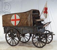 Een ziekenwagen uit WO I. Je ziet ook de vlag van het Rode Kruis.