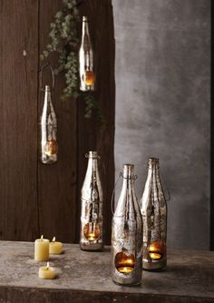 These antiqued mercury glass bottles are actually recycled beer bottles transformed & restyled! Inside is a metal cup tea light holder & the bottle is topped with an iron wire loop for hanging. I love this look.