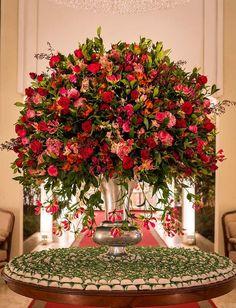 Mesa de bem-casados com arranjo alto de flores vermelhas, rosas e folhagem Madame Fiori