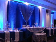Royal blue satin with white pintuck runners, white organza sequins table overlay, cake table with metallic lace sequin overlay. Candelabras