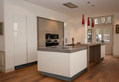 White high gloss handleless kitchen design with floating kitchen island effect.