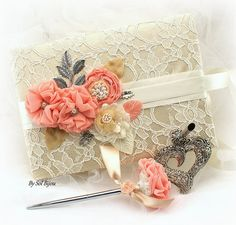 ***Made Upon Request- This set can be made in ANY color scheme  This guest book and signing pen set is a gorgeous combination of ivory, champagne, coral, tan and silver. The book has been covered in ivory lace over champagne fabric. Beautiful handmade flowers, pearls, crystal jewels and silverleaves make this set irresistible.  Large size: 10 inches from left to right and 7 inches wide (from top to bottom) It has 100 pages (front and back) and 2600 lines for signatures. The small size is 7.5…