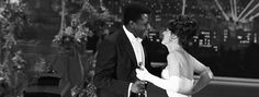 """The 36th Academy Awards (1964). Best Actor Sidney Poitier (""""Lilies of the Field"""") accepts his Oscar from Anne Bancroft."""