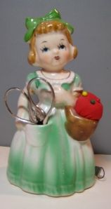 This sweet little girl will hold your scissors and pins.