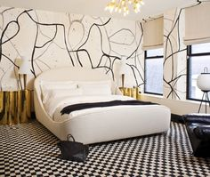 Black and grey painterly strokes and splatters create interest in this minimally furnished guest bedroom. Wearstler's effective colour palette of black, white and gold emanates luxury at its finest.