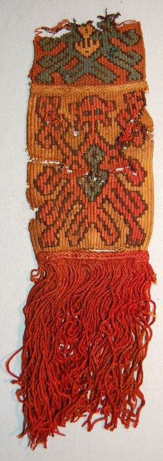 Nazca-Huari textile fragment; 2 pieces attatched together(?) with fringing at 1 end; main portion is slit tapestry with zoomoprhic figure with multiple ...