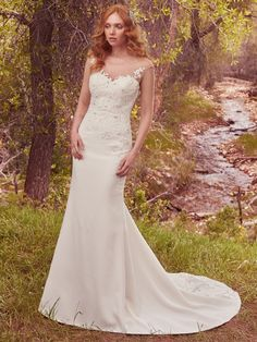 This gorgeous sheath features a bodice embellished with lace appliqués and delicate pearls and Swarovski crystals, flowing into a simple Sylvie crepe skirt. An illusion sweetheart neckline complements an illusion keyhole-back accented in lace appliqués. Finished with covered buttons over zipper closure.