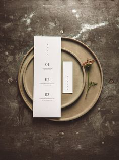 Alternative minimal wedding day menu and vertical name card on organic feel paper on olive green earthenware and a zinc table. Moody and meaningful wedding inspiration by Hilde.