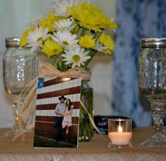 DIY country wedding. Daisies in mason jars, mason jar wine glasses for bride and groom and personalized pictures for each table. Each table was also a different country music artist instead of numbers.