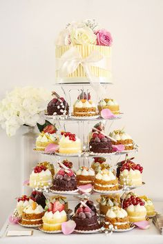 Love this! A cake on top of individual, fancy little cakes.