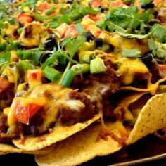 Nachos topped with a ground beef and bean mixture, with cheese, tomatoes and onions.