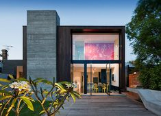 modern remodel addition on back of house.  View from garden, Pivot doors create large expanse  to look into home & upper wall is used to hang large piece of art adding colour to neutral wood & concrete exterior, by Nixon Tulloch Fortey