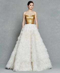 Feathered wedding dresses are such a trendy style that modern brides should embrace, and what better way to do that than in this exquisite Kelly Faetanini gold wedding dress. The contrast between the crisp white feathers and structured bodice give off a really festive look making this design the perfect winter wedding dress.