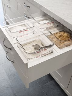A drawer just below the kitchen counter to hold canisters of frequently used ingredients. Containers sealed, but easily accessible and removable for cleaning.