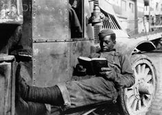 An African American soldier reads a book while resting on an A.T.S. salvage truck, shortly after World War I. Saint-Nazaire, France, April 6, 1919.  Great Picture!! lol doesn't look like a comfy seat so must be a really good book!