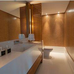 Lavabo, com papel de parede que imita couro e divisória de madeira.