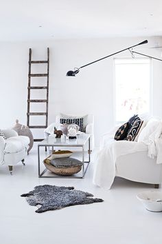 Love the ethnic pieces with modern white; great light fixture and rustic ladder