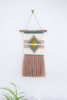 This listing is for a wall hanging perfect for anywhere in your house. This weaving has a cream and beige striped design with a duck egg blue, dusty pink, and mustard yellow diamonds in the centre. A piece of locally sourced driftwood acts as the dowel.