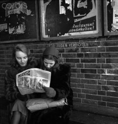 """From the series """"Conditions in Berlin after the War:"""" Two young women read the newspaper in front of the writing """"Fuer Juden verboten"""" (Jews prohibited) in Berlin, Germany, December 1945. Photo: Deutsche Fotothek / Fritz Eschen - NO WIRE SERVICE"""