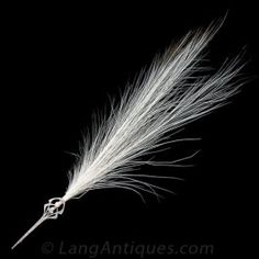 Ultra rare and exotic. This turn-of-the-century treasure is designed to display a feather plume from usually an Egret or Heron (it also looks beautiful without). Although typically associated with the Jazz Age, this piece dates back to the late Victorian / early Edwardian period. Composed of platinum over 14 karat yellow gold set with old-mine and rose-cut diamonds and a central Oriental button pearl. This enchanting and historical jewel measures 3 3/8 inches long.