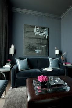 Dark grey living room with matching dark grey ceiling and lighter rug but still with grey/blue tones. Accent of pink.