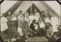 Photograph: Nursing sisters and patients outside a ward tent, No. 2 Canadian General Hospital, Le Tréport, France. Note the dog with a bandaged paw sitting at the centre of the group; both dog and master have pipes in their mouths.