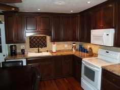 Rich Mahogany Cabinets only I'd like it with black appliances and the cherry hardwood floors.
