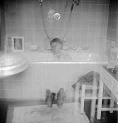 Lee Miller in Hitler's apartment at 16 Prinzregent Note the combat boots on the bath mat now stained with the dust of Dachau; and a photograph of the previous owner of the flat propped on the edge of the tub. - 2244 | LeeMiller