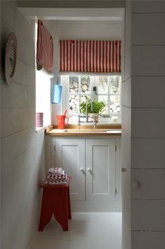 More of the simple kitchen...love the red and white stripes roman shades....