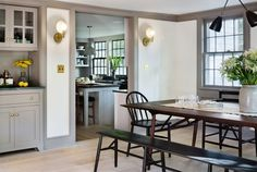 Rafe Churchill renovated Bedford NY farmhouse - modern-farmhouse-renovation-dining-room-kitchen-brass-sconces-built-in-storage Farmhouse Renovation, Farmhouse Remodel, Modern Farmhouse Kitchens, Farmhouse Table, Grey Kitchens, Dark Trim, Grey Trim, Weekend House, Painting Trim