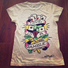 "Ed Hardy ""love is a gamble"" white shirt size small This is an Ed Hardy by Christian Audigier size small 100% cotton shirt. It is in excellent condition and a fitted shirt. The shirt is white with black writing and pink, yellow, green and red on the front print with red glitter. If you have any questions please ask! Ed Hardy Tops Tees - Short Sleeve"