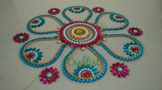 Blue & pink flower rearrangeable rangoli 275 Rs 12 outer pieces (6 big +6 small) & 2 middle pieces Material ohp sheet & kundan ,coloured chains