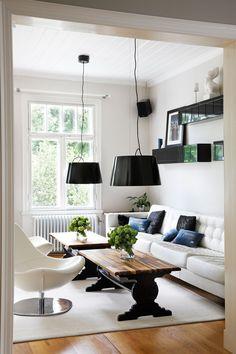 Olohuoneen mustat valaisimet, nojatuolit ja valkoinen sohva on ostettu Ikeasta. Kulmasohva on muutettu yhdeksi pitkäksi sohvaksi. VM-Carpetin villamaton päällä on Thomaksen valmistamat sohvapöydät. Pöydänjalat on tehty liimapuulevystä ja kansi eurooppalaisesta saksan- pähkinäpuusta.