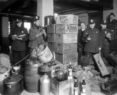Officers admire a cache of alcohol captured during a raid. At right are a pile of suitcases, presumably used to transport the contraband throughout Detroit.